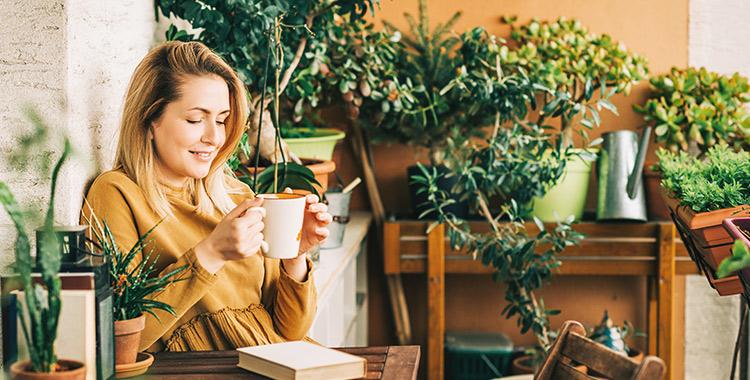 Mulher tomando café e lendo um livro na varanda