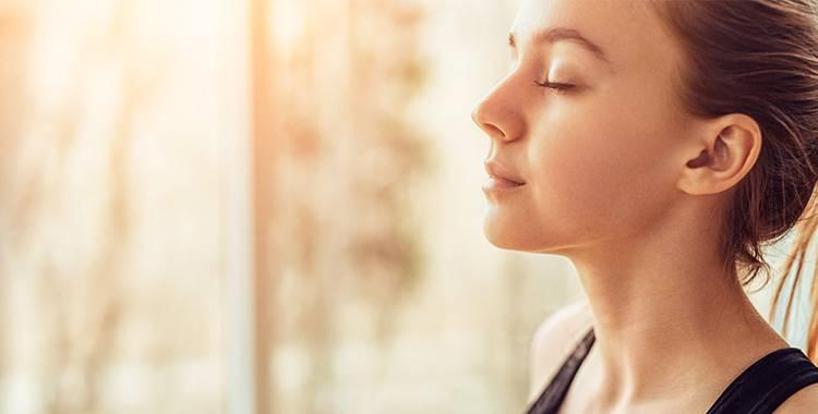 Mulher praticando a respiração para acalmar seus pensamentos
