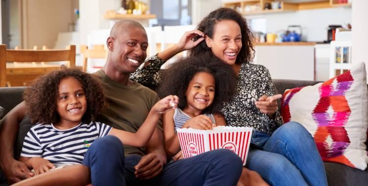 Pais assistindo filme com seus filhos no dia das mães