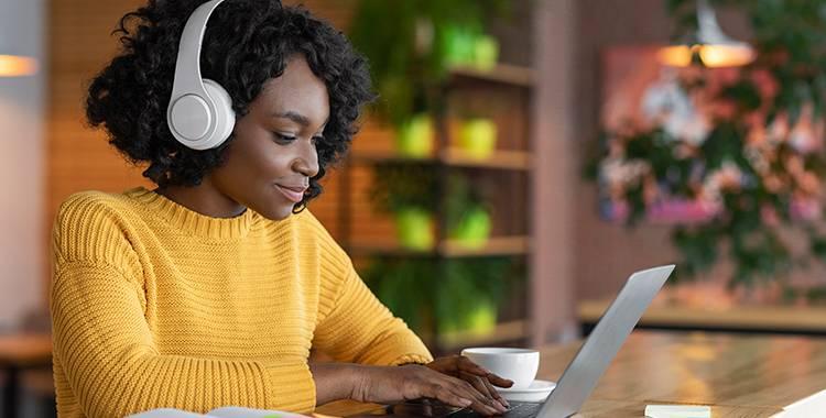 Mulher escutando música em um cafeteria enquanto trabalha