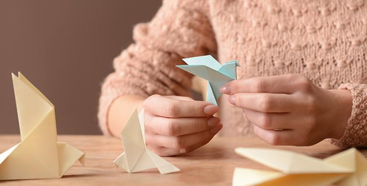 mulher fazendo origami em dobradura