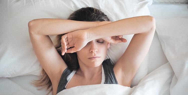 Mulher deitada na cama tentando dormir