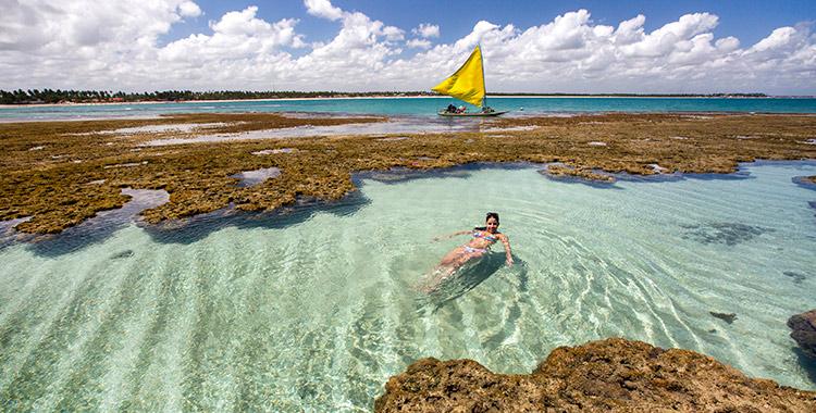 Mulher nadando em uma piscina natural no Porto de Galinhas em Pernambuco