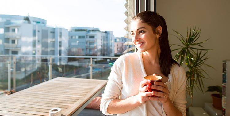 mulher aproveitando a luz do sol dentro de casa enquanto toma café