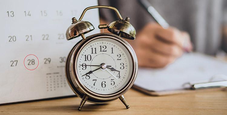 Foto com um relógio e um calendário em cima da mesa e uma pessoa ao fundo escrevendo em um caderno, ilustrando o planejamento da rotina