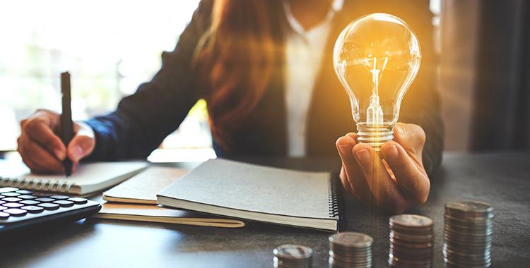mulher sentada em frente a uma mesa fazendo anotações em um caderno e segurando uma lâmpada com a outra mão.