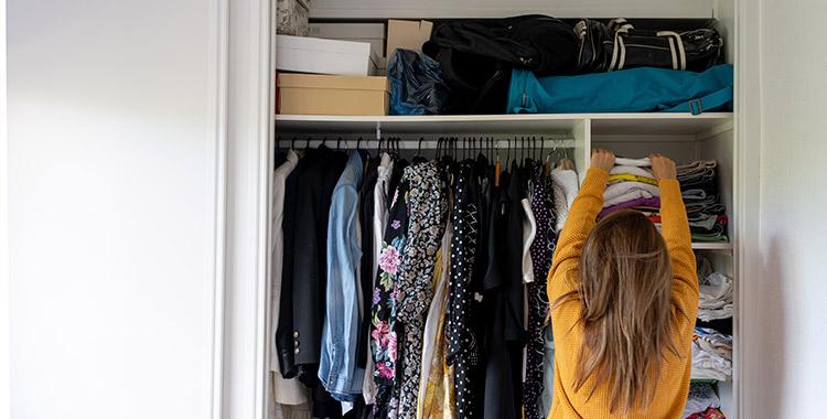 Mulher em frente ao guarda-roupa com as mãos levantadas verificando se existe mofo