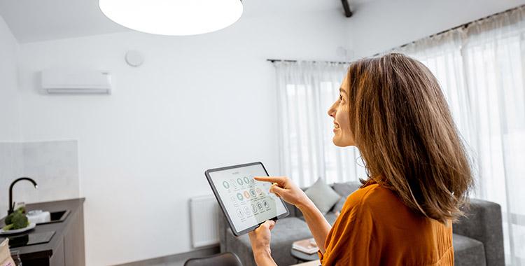 uma fotografia de uma mulher em pé, no centro da sala, segurando um tablet com as mãos e tocando na tela para acender a luz de uma residência automatizada