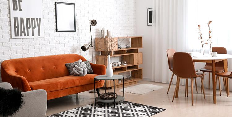 """Uma fotografia de uma sala com um sofá, uma mesa, cadeiras, uma mesa de centro e um armário no canto da sala. Na parede com textura de tijolos, um quadro com a frase """"Be Happy"""". No chão, um tapete. É um exemplo de projeto de Neuroarquitetura."""