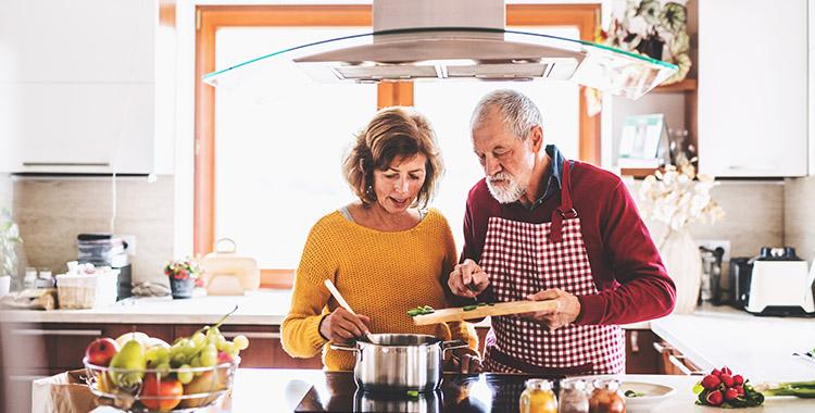 Uma fotografia com duas pessoas cozinhando. Temos uma coifa para eliminar a gordura e a fumaça do ar.