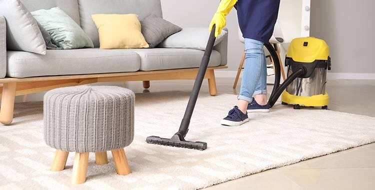 Uma fotografia de uma pessoa passando o aspirador de pó no tapete da sala.