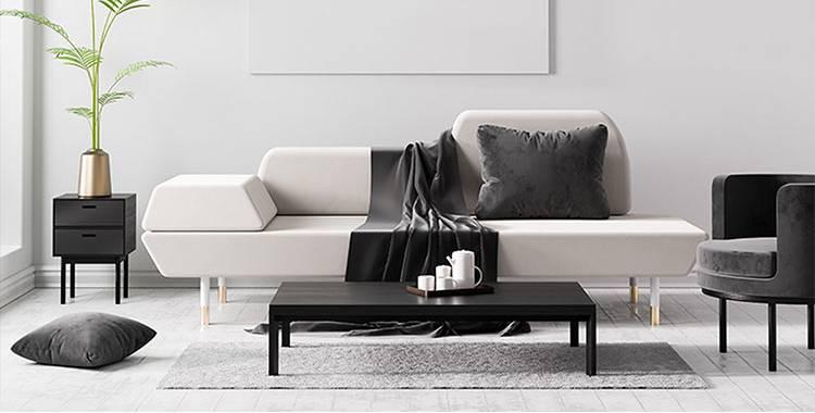 Uma fotografia de uma sala com um sofá, uma mesinha no canto com uma planta, luminária pendente e uma poltrona. Um exemplo de decoração minimalista.