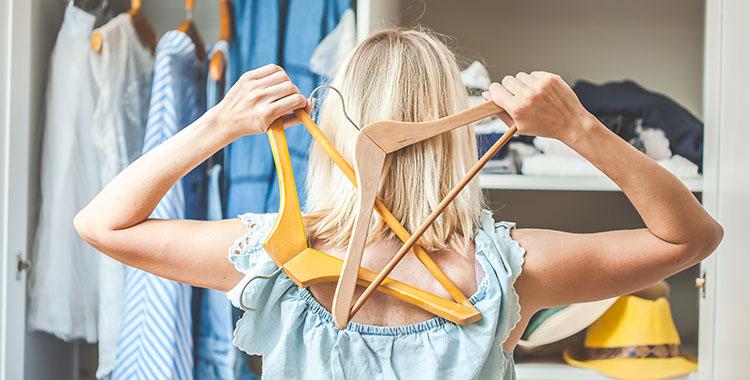 Uma fotografia de uma mulher de costas, segurando dois cabides e olhando para um guarda-roupa.