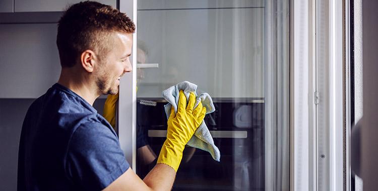 Uma fotografia de um homem limpando uma janela de vidro.