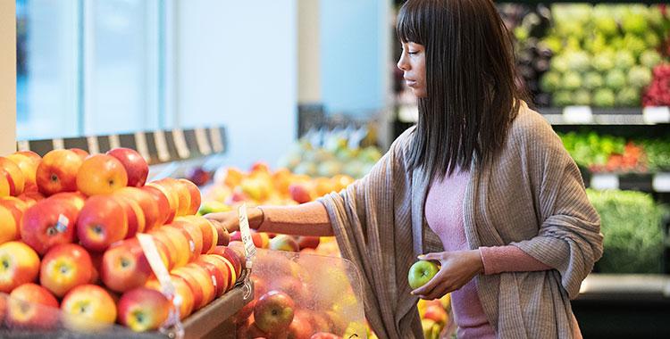 Uma fotografia de uma mulher escolhendo frutas.