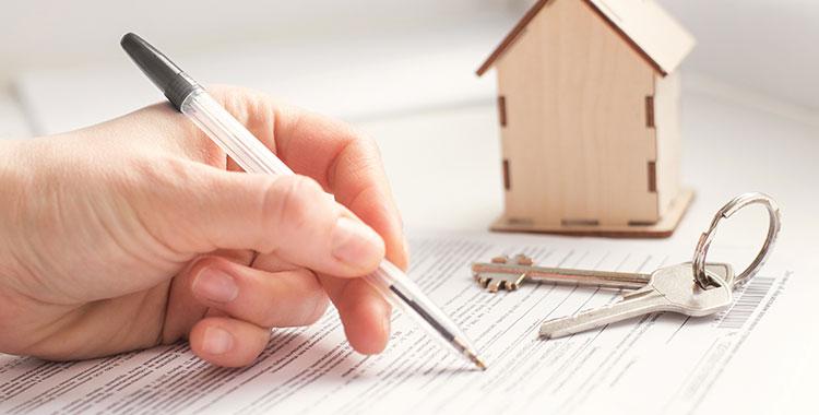 Uma fotografia de uma mão segurando uma caneta sobre um documento sobre uma mesa, que está próximo a uma chave e uma casa esculpida em madeira.