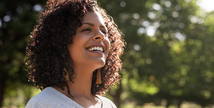 Uma fotografia de uma mulher sorrindo em um local arborizado.