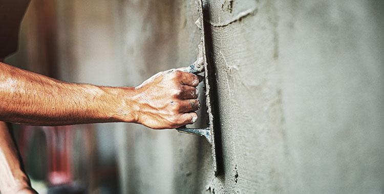 Uma fotografia com uma mão enquadrada passando massa de construção na parede.