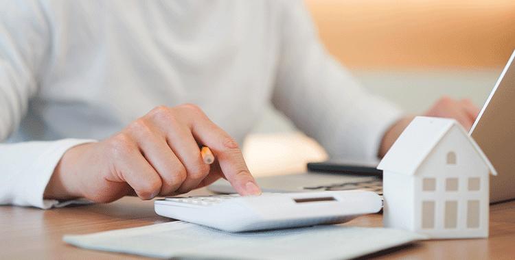 Homem fazendo cálculos em uma calculadora sobre investimento imobiliário