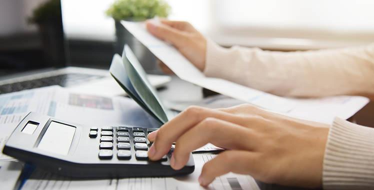 Uma fotografia em plano fechado com uma mão digitando em uma calculadora