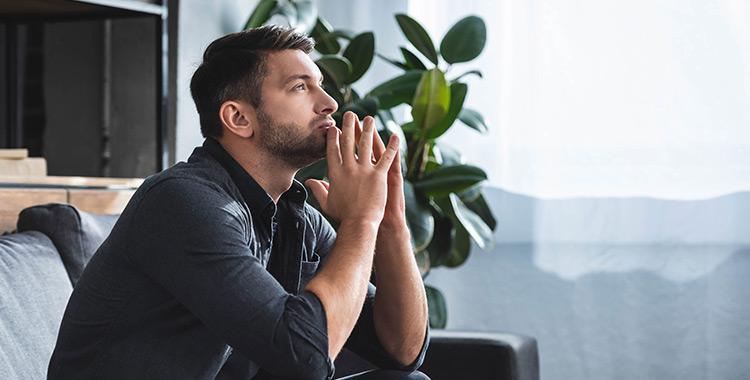 Uma fotografia de um homem sentado pensativo com as mãos no queixo
