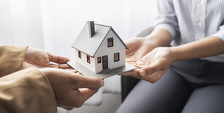 Uma fotografia com duas pessoas segurando uma miniatura de uma casa.