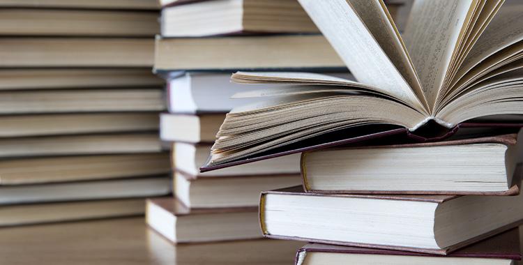 Uma fotografia com pilhas de livros sobre a mesa