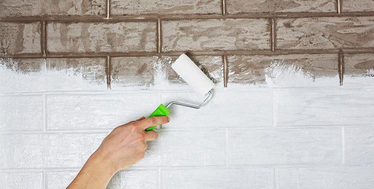 Uma fotografia de uma parede com azulejos sendo pintada.
