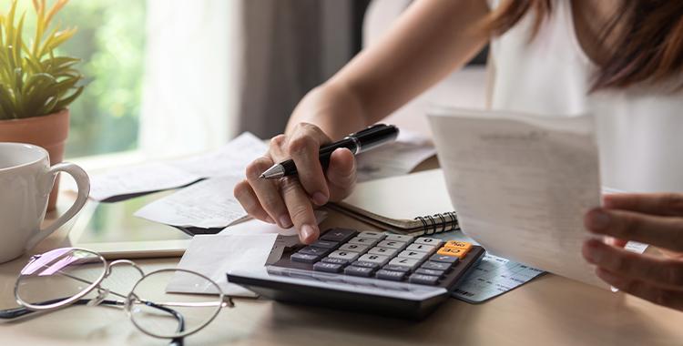 Uma fotografia de uma pessoa usando uma calculadora para fazer contas.