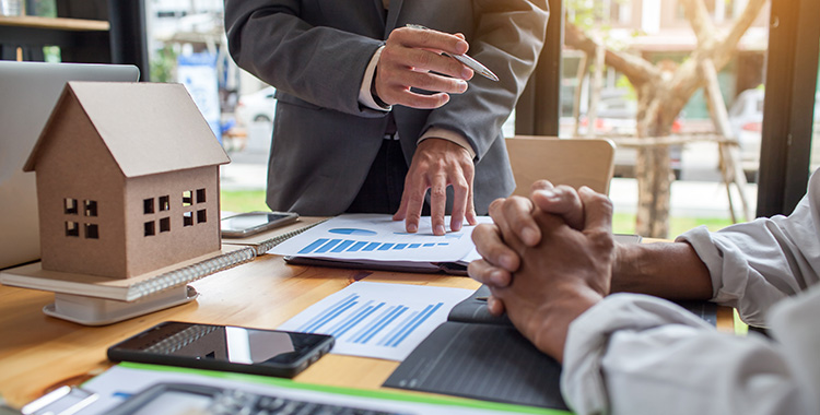 Uma fotografia com duas pessoas em volta de uma mesa com papéis, calculadoras e uma miniatura de casa.