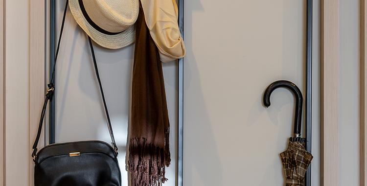 Uma fotografia que ilustra ganchos com bolsas e chapéus pendurados.