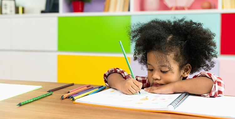 Uma imagem que ilustra uma criança sentada desenhando.