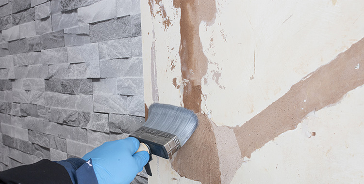 Uma imagem que ilustra uma pessoa passando cola na parede.