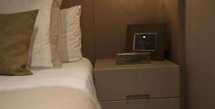 Uma fotografia que ilustra um cama com cabeceira de madeira.
