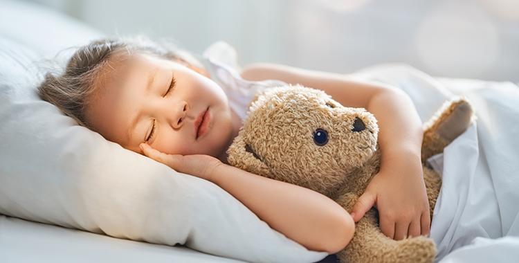 Uma fotografia de uma criança dormindo com um ursinho de pelúcia