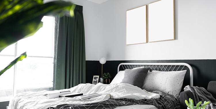 Uma fotografia que ilustra uma cama e um cabeceira em um quarto.