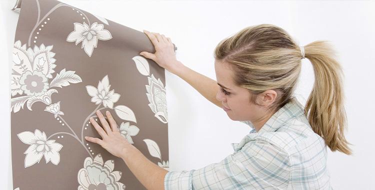 mulher aplicando papel de parede floral na parede
