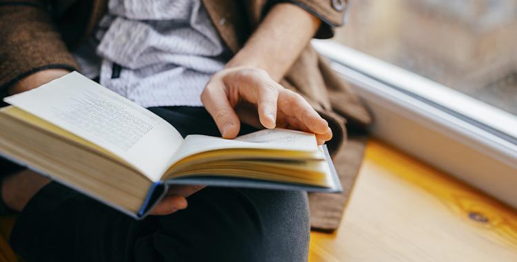 Uma fotografia que ilustra um homem lendo um livro