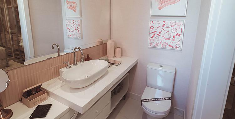 Uma fotografia de um banheiro decorado com quadros.