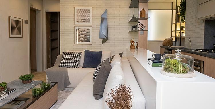Uma fotografia que ilustra uma sala e uma cozinha americana com quadros na parede.